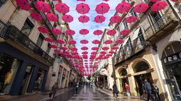 Pejalan kaki melintasi ratusan payung pink yang digantung sebagai tanda dukungan atas kewaspadaan bahaya kanker payudara di Montpellier, Prancis, Selasa (9/10). Bulan Oktober, ditetapkan sebagai bulan kewaspadaan atas kanker payudara. (AFP/PASCAL GUYOT)