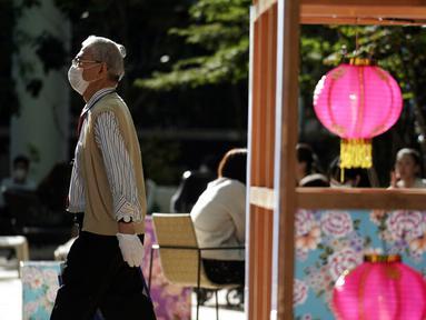 Seorang pria yang mengenakan masker pelindung untuk membantu mengekang penyebaran virus corona COVID-19 berjalan di Tokyo, Jepang, Senin (12/10/2020). Tokyo mengonfirmasi lebih dari 70 kasus COVID-19 pada hari Senin. (AP Photo/Eugene Hoshiko)