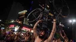 Seorang pria telanjang sambil mengangkat sepedanya saat melakukan aksi di Sao Paulo, Brasil (10/3). Mereka menuntut agar kondisi jalan kota lebih baik, serta meningkatkan kesadaran akan keselamatan pengendara sepeda. (AFP/Nelson Almeida)