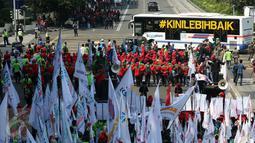 Bus Transjakarta melintas di depan massa buruh yang melakukan aksi peringatan May Day di Jalan MH Thamrin, Jakarta, Senin (1/5). Sambil meneriakkan aspirasinya, massa buruh mulai bergerak menuju Istana Negara. (Liputan6.com/Johan Tallo)