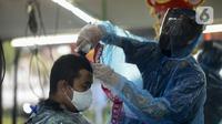 Tukang cukur mengenakan alat pelindung diri (APD) dari plastik saat mencukur rambut pelanggan di Pondok Kelapa, Jakarta, Selasa (5/5/2020). Tukang cukur mengenakan APD untuk mengurangi risiko penularan virus corona COVID-19. (merdeka.com/Imam Buhori)