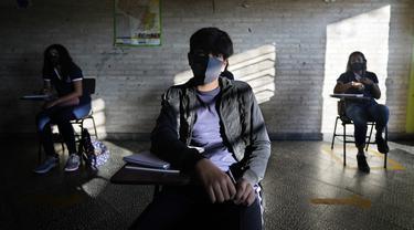 Murid kelas delapan duduk berjauhan pada hari pertama sekolah tatap muka di National School 1044 Santa Ana, Asuncion, Paraguay, Senin (30/8/2021). Sekolah tatap muka digelar setelah satu setengah tahun belajar jarak jauh di tengah pandemi COVID-19. (AP Photo/Jorge Saenz)