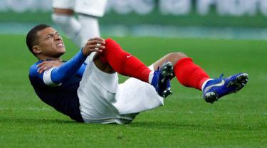 Penyerang timnas Prancis dan PSG, Kylian Mbappe meringis kesakitan setelah terlibat duel dengan kiper timnas Uruguay, Martin Campana dalam laga uji coba di Stade de France, Rabu (21/11). Mbappe mengalami cedera bahu pada menit ke-30 (AP/Francois Mori)
