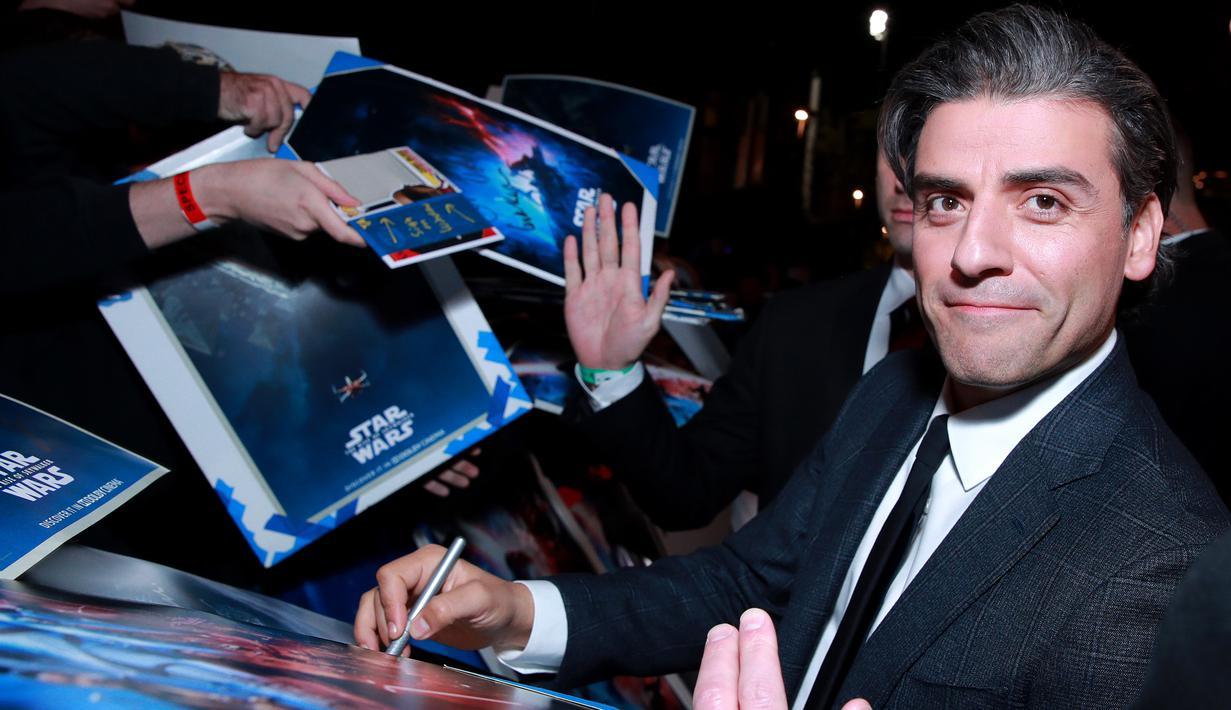 "Aktor Oscar Isaac memberikan tanda kepada penggemar saat menghadiri pemutaran perdana ""Star Wars: The Rise Of Skywalker"" di Hollywood, Senin (16/12/2019). The Rise Of Skywalker sendiri mengisahkan pertarungan antara terang dan gelap, Rey dan Kylo Ren. (Rich Fury/Getty Images/AFP)"