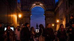 Orang-orang menunggu menyeberang jalan di Rua Augusta Arch di Lisbon (17/12). Penduduk kota ini berjumlah 600.000 jiwa dan di daerah metropolitan sekitar 2,5 juta jiwa. Jumlah ini kira-kira 1/3 penduduk Portugal. (AFP Photo/Patricia De Melo Moreira)