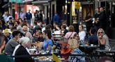 Pelanggan menikmati makan siang di meja di luar restoran di Soho, London, ketika pemerintah Inggris mempertimbangkan pembatasan baru pada Minggu (20/9/2020). Inggris kemungkinan akan kembali memberlakukan tindakan lockdown akibat lonjakan tajam infeksi virus corona COVID-19. (DANIEL LEAL-OLIVAS/AFP)