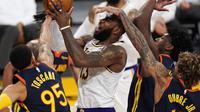 Bintang Los Angeles Lakers, LeBron James, saat berusaha menembak bola di tengah kepungan pemain Golden State Warriors, Senin (1/3/2021) pagi WIB. (AP Photo/Mark J. Terrill)