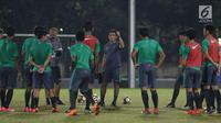 Pelatih Timnas Indonesia U-19, Bima Sakti (tengah) memberi arahan saat latihan perdana jelang laga melawan Jepang U-19 di Lapangan A Kompleks GBK, Jakarta, Kamis (22/3). Laga kedua tim akan digelar Minggu (25/3). (Liputan6.com/Helmi Fithriansyah)