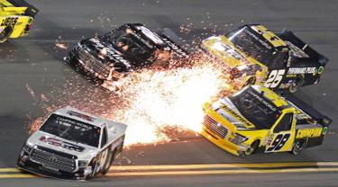 Percikan api terlihat saat terjadi serempetan di arena perlombaan balap Nascar Truck Series di Daytona International Speedway di Daytona Beach (16/2). (AP Photo/Darryl Graham)