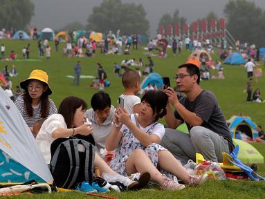 Orang-orang berswafoto saat berkemah di gunung yang indah di Yanqing, pinggiran Beijing pada 30 Agustus 2020. China memiliki lebih dari 200 orang yang dirawat di RS karena COVID-19, dengan lebih dari 300 lainnya diisolasi setelah dites positif terkena virus tanpa menunjukkan gejala. (AP/Andy Wong)