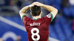 Pemain Wolverhampton Wanderers, Ruben Neves, memegang kepalanya saat melawan Brighton and Hove Albion pada laga Liga Inggris di Stadion Amex, Sabtu (2/1/2021). Kedua tim bermain imbang 3-3. (Gareth Fuller/POOL/AFP)