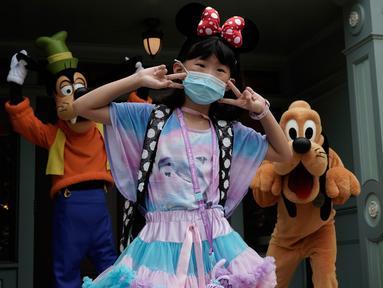 Seorang pengunjung yang mengenakan masker berswafoto dengan karakter kartun Goofy dan Pluto di Disneyland Hong Kong pada Jumat (25/9/2020). Setelah dibuka dan tutup kembali, Disneyland Hong Kong dibuka kembali untuk wisatawan . (AP Photo/Kin Cheung)