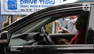 """Petugas Amil Zakat melayani warga yang membayar zakat fitrah melalui sistem """"drive thru"""" di Masjid Nurul Hidayah, Tanah Kusir, Jakarta, Selasa (19/5/2020). Layanan zakat """"drive thru"""" selama pandemi COVID-19 ini diberlakukan dengan protokol kesehatan dan keselamatan. (Liputan6.com/ Johan Tallo)"""