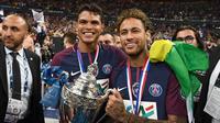 Penyerang PSG, Neymar Jr dan Thiago Silva tersenyum sambil membawa Piala Prancis di Saint-Denis, Paris (8/5). Meski dalam kondisi cedera, Neymar tetap hadir menyaksikan timnya bertanding di final melawan Les Herbiers.  (AFP Photo/Franck Fife)
