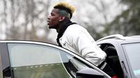 Gelandang Prancis Paul Pogba keluar dari mobil saat tiba di markas timnas sepak bola Prancis di Clairefontaine-en-Yvelines, (19/3). Pogba tampil dengan gaya rambut yang baru dengan warna emas dan hijau. (AFP Photo/Franck Fife)