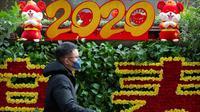 Seorang pria yang mengenakan masker melewati layar perayaan Imlek Tahun Tikus Logam di Stasiun Kereta Api Barat Beijing, 21 Januari 2020. Pihak berwenang China mengonfirmasi telah ada empat orang yang meninggal akibat terinfeksi virus corona jenis baru di pusat kota Wuhan. (AP/Mark Schiefelbein)