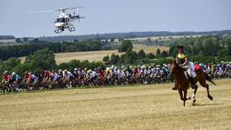 Seorang wanita menunggang kuda mengikuti pebalap  pada etape ketujuh Tour de France yang memiliki jarak tem[puh 213,5 km antara Troyes dan Nuits-Saint-Georges, (7/7/2017). (AFP/Philippe Lopez)