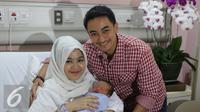Gubernur Jambi Zumi Zola dan istri, Sherrin Tharia, berpose usai menggelar jumpa wartawan terkait kelahiran anak ke 2 di RS Pondok Indah, Jakarta, Kamis (23/6). (Liputan6.com/Herman Zakharia)