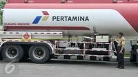 Petugas polisi memeriksa garis polisi yang terpasang di truk pengisian bahan bakar solar di SPBU Jalan Juanda, Depok, Senin (14/11). SPBU itu ditutup sementara karena salah satu pompa bahan bakar solarnya diduga bercampur air. (Liputan6.com/Yoppy Renato)