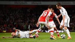 Gelandang Swansea City, Gylfi Sigurdsson (kanan) berusaha melewati dua pemain Arsenal saat Laga Liga Premier Inggris di Emirates Stadium, Selasa (12/5/2015). Swansea City menang 1-0 atas Arsenal. (Reuters/ADylan Martinez)