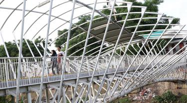 Pejalan kaki melintasi jembatan penyeberangan orang (JPO) Jayakarta yang atapnya rusak dan hilang di Menteng, Jakarta, Jumat (11/1). Kondisi atap JPO yang rusak akibat tertiup angin mengganggu kenyamanan pejalan kaki. (Liputan6.com/Immanuel Antonius)