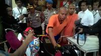 Salah satu tersangka curas motor di Garut, tengah mempraktekan adegan mencuri motorj (Liputan6.com/Jayadi Supriadin)