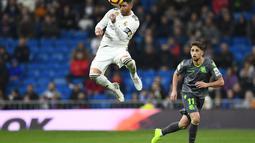 2. Aksi sundulan dari Sergio Ramos pada laga lanjutan La Liga Spanyol yang berlangsung di Stadion Santiago Bernabeu, Madrid, Senin (7/1). Real Madrid kalah 0-2 kontra Real Sociedad. (AFP/Gabriel Bouys)