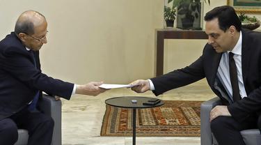 PM Lebanon, Hassan Diab (kanan) mengajukan pengunduran dirinya kepada Presiden Michel Aoun di istana presiden di Baabda, ibu kota Beirut pada 10 Agustus 2020. Pengunduran diri Diab dilakukan di tengah kemarahan rakyat atas ledakan besar di Beirut pada 4 Agustus lalu. (HO/DALATI AND NOHRA/AFP)