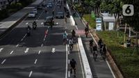 Sejumlah pesepeda melintasi jalur kendaraan bermotor saat uji coba pembatas jalur sepeda permanen di kawasan Sudirman, Jakarta, Minggu (28/2/2021). Uji coba berlangsung selama tahap penyempurnaan jalur sepeda permanen yang ditargetkan rampung akhir Maret 2021. (Liputan6.com/Johan Tallo)