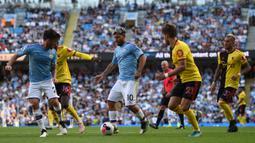 Striker Manchester City, Sergio Aguero, berusaha melewati kepungan pemain Watford pada laga Premier League di Stadion Etihad, Manchester, Sabtu (21/9). City menang 8-0 dari Watford. (AFP/Oli Scarff)
