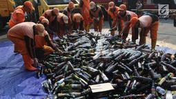 Petugas memusnahkan barang bukti miras dan narkoba di halaman Polsek Palmerah, Jakarta Barat, Senin (14/5). Pemusnahan dilakukan untuk menciptakan suasana kondusif menjelang bulan suci Ramadan. (Liputan6.com/Arya Manggala)