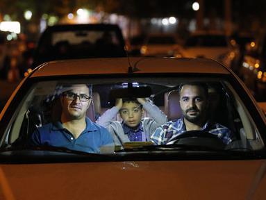 Warga duduk dalam mobil saat upacara keagamaan pada bulan suci Ramadan di tengah pandemi COVID-19, Teheran, Iran, Kamis (30/4/2020). Keluarga-keluarga di Iran menghadiri upacara keagamaan drive-in karena tidak memiliki kesempatan untuk salat di masjid setelah berbuka puasa. (STR/AFP)