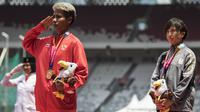 Atlet lompat jauh Indonesia, Rica Oktavia, hormat bendera saat seremoni usai meraih medali emas Asian Para Games 2018 di SUGBK, Jakarta, Senin (8/10/2018). (Bola.com/Vitalis Yogi Trisna)