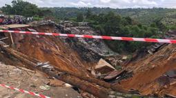 Permukaan jalan ambruk oleh tanah longsor yang disebabkan hujan lebat melanda distrik Lemba, Kinshasa di Republik Demokratik Kongo pada Selasa (26/11/2019). Menurut seorang pejabat terkemuka di Kota Kinshasa, ada tiga puluh enam orang tewas tertimbun tanah longsor. (AFP/Ange Kasongo)