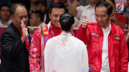 Presiden Joko Widodo mengacungkan jempol memberi semangat atlet wushu Indonesia, Lindswell Kwok saat bertanding di Asian Games 2018, Jakarta, Senin (20/8). Lindswell menyumbang emas kedua untuk Indonesia. (Bola.com/Vitalis Yogi Trisna)