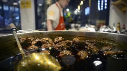 Koki menyiapkan menu kepala kelinci di sebuah restoran di Chengdu, ibu kota Provinsi Sichuan di barat daya China, 8 September 2016. Otak kelinci di negeri tirai bambu ini menjadi salah satu menu favorit warga lokal maupun asing. (WANG ZHAO/AFP)