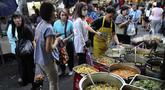 Karyawan perempuan membeli makanan sebelum mereka pergi bekerja di sebuah gang, yang terkenal dengan pedagang kaki lima dan pakaian, di pusat Bangkok, Thailand (8/11/2019). (AP Photo/Aijaz Rahi)