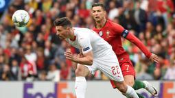 Penyerang Portugal, Cristiano Ronaldo, berebut bola dengan bek Swiss, Fabian Schar, pada laga UEFA Nations League di Estadio Do Dragao, Porto, Kamis (6/6) dini hari WIB. Portugal menang 3-1 atas Swiss. (AFP/Miguel Riopa).