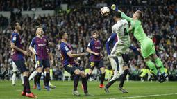 Kiper Barcelona, Marc-Andre ter Stegen, duel udara dengan bek Real Madrid, Sergio Ramos, pada laga La Liga di Stadion Santiago Bernabeu, Sabtu (2/3). Real Madrid takluk 0-1 dari Barcelona. (AP/Manu Fernandez)