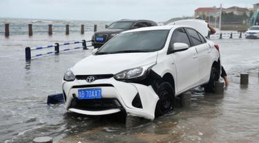 Sebuah mobil rusak setelah dihantam ombak yang disebabkan Topan Yagi di sepanjang pantai laut di Qingdao di provinsi Shandong timur China (13/8). Lebih dari 200.000 warga mengungsi saat topan mencapai daratan pantai timur. (AFP Photo)