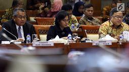 Menkeu Sri Mulyani (tengah) didampingi Menteri PPN/Kepala Bappenas Bambang Brodjonegoro (kanan), dan Gubernur BI Perry Warjiyo (kiri) mengikuti rapat kerja bersama Komisi XI, di Kompleks Parlemen, Senayan, Jakarta, Rabu (16/1). ( Liputan6.com/JohanTallo)