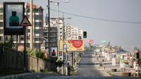 Warga Palestina berjalan di jalan sepi di tepi pantai pada awal pemberlakukan lockdown total selama 48 jam di Kota Gaza, Selasa (25/8/2020). Lockdown dan jam malam diberlakukan di wilayah jalur Gaza menyusul terkonfirmasinya kasus Covid-19 pertamanya di sebuah kamp pengungsian. (MOHAMMED ABED/AFP)