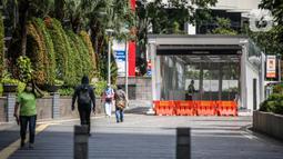 Warga berjalan kaki di trotoar kawasan Sudirman, Jakarta, Kamis (4/6/2020). Gubernur DKI Jakarta Anies Baswedan memperpanjang penerapan Pembatasan Sosial Berskala Besar (PSBB) dan menetapkan bulan Juni sebagai masa transisi Ibu Kota di masa pandemi. (Liputan6.com/Faizal Fanani)
