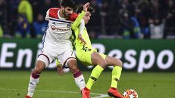 Duel gelandang Lyon, Martin Terrier dan Sergi Roberto pada leg 1, babak 16 besar Liga Champions yang berlangsung di stadion Parc Olympique Lyonnais, Lyon, Rabu (20/2). Barcelona bermain imbang 0-0 kontra Lyon. (AFP/Franck Fife)