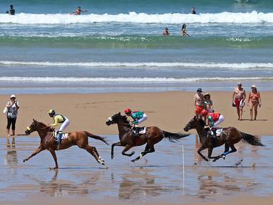 Para joki beraksi dalam kejuaraan tahunan pacuan kuda pantai di Loredo, Santander, Spanyol, (24/7/2016). (AFP/Cesar Manso)