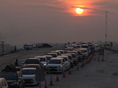 Kendaraan melintas saat matahari terbenam untuk keluar dari ruas Tol Batang-Semarang menuju jalur Pantura Batang-Kendal di Kali Kuto, Gringsing, Batang, Jawa Tengah, Senin (11/6). (Liputan6.com/Arya Manggala)