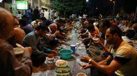 Warga muslim Iran menikmati menu makanan berbuka puasa di sebuah jalan di Teheran, 29 Mei 2018. Sebagian besar warga muslim Iran melaksanakan ibadah puasa di bulan Ramadan sesuai ajaran Islam melalui Nabi Muhammad. (AP Photo/Vahid Salemi)