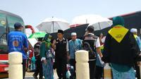 Petugas haji jadi ojek payung bagi jemaah Indonesia. (MCH Indonesia/Dream)