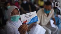Warga menunjukkan kartu vaksinasi Covid-19 usai mengikuti vaksin di SDN Grogol Utara 09 Pagi, Jakarta, Sabtu (28/8/2021). Vaksinasi yang diikuti 1.000 peserta merupakan kolaborasi yang sejalan dengan semangat RYTHM dari QNet dalam meningkatkan kesehatan masyarakat Indonesia. (Liputan6.com/HO/QNet)