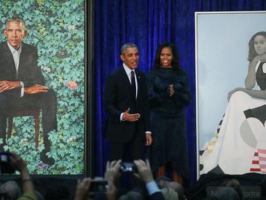 Presiden AS ke-44 Barack Obama bersama istrinya Michelle Obama berdiri di samping lukisan mereka berdua saat upacara peresmian di Galeri Potret Nasional Smithsonian, Washington DC (12/2). (Mark Wilson/Getty Images/AFP)